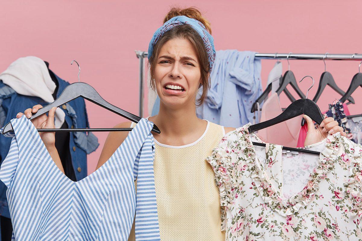 Frau schaut verzweifelt in die Kamera und hält zwei Kleiderbügel mit Kleidern in der Hand. Sie weiß nicht was sie zum Vorstellungsgespräch anzeihen soll.