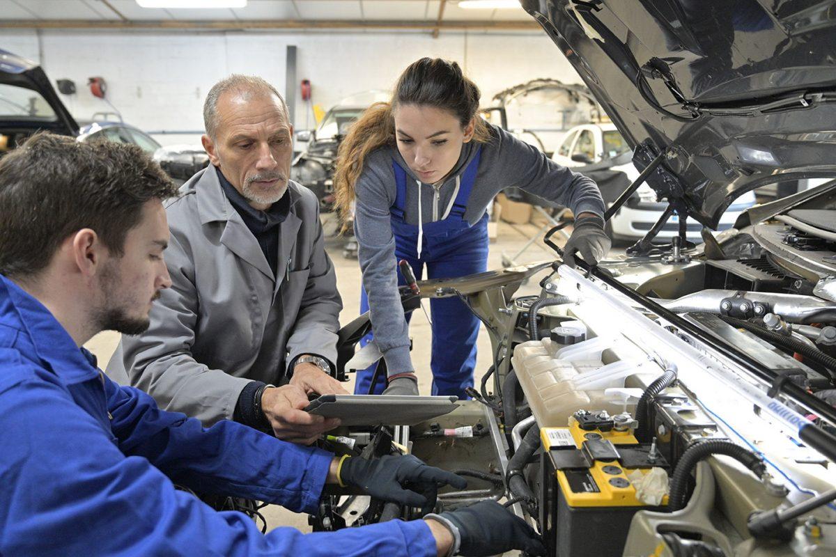 Ein Ausbilder zeigt zwei Auszubildenden einen Motor.