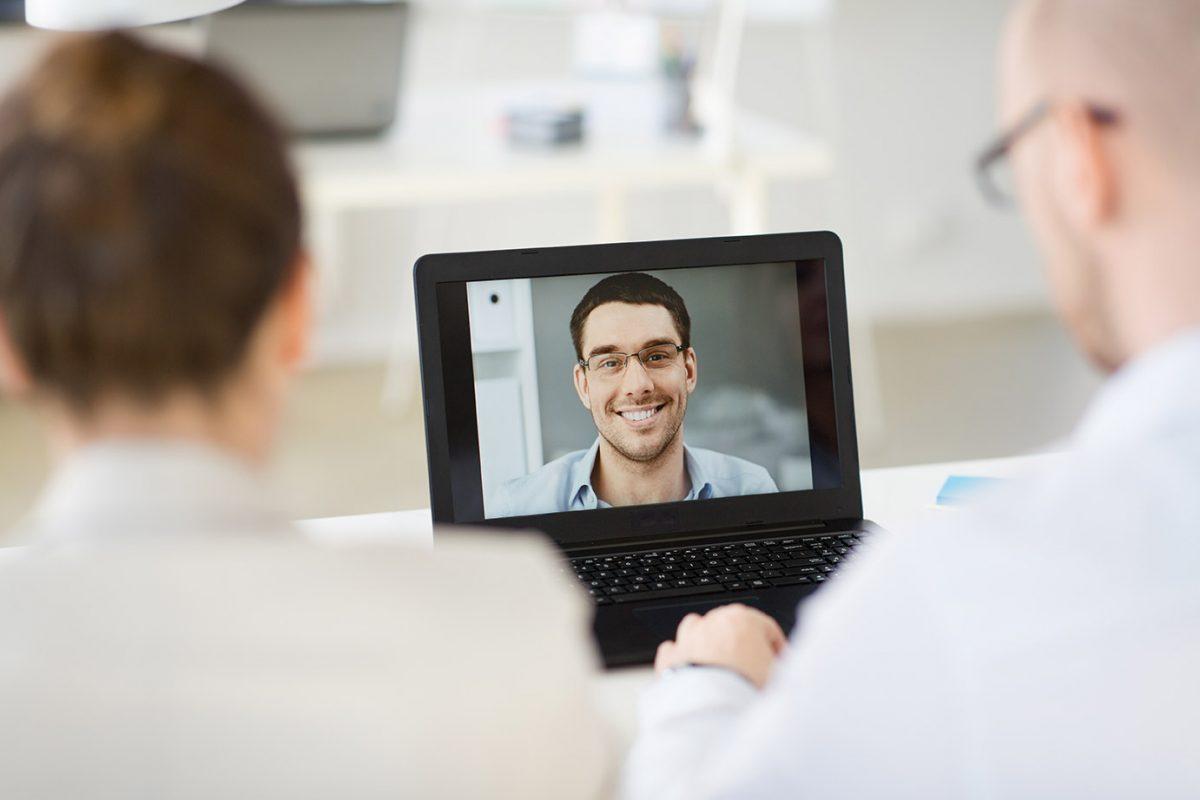 Online Vorstellungsgespräch mit zwei Personen vor dem Laptop und einem jungen Mann, der per Video zugeschaltet ist.
