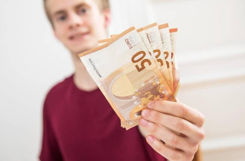 Junge im Hindegrund der fünf 50 Euro Scheine in der Hand hält.